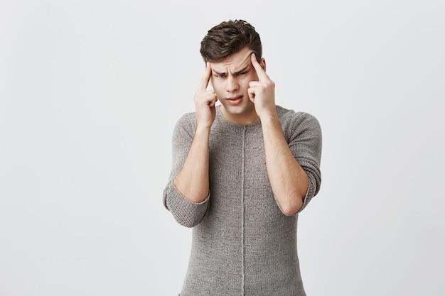 Pensoso bell'uomo caucasico vestito in maglione, tiene le dita sulle tempie, guarda seriamente, medita, cerca di trovare la decisione adatta in situazioni difficili. persone, giovani, concetto di lifestyle Foto Gratuite