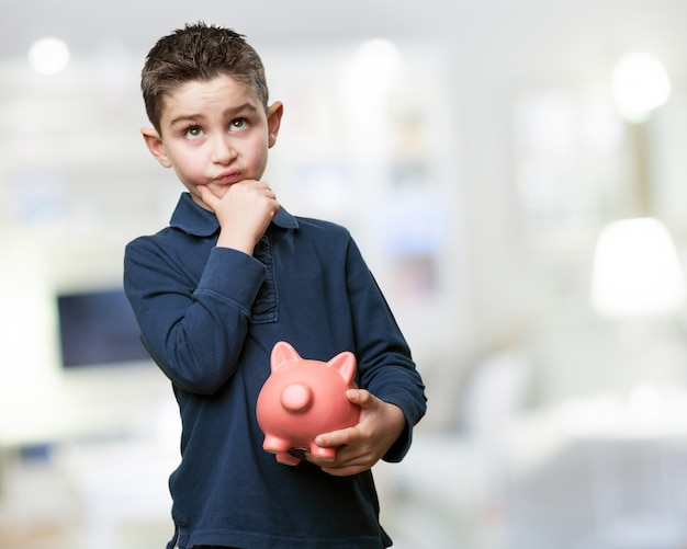 Pensive child with a piggy bank Free Photo