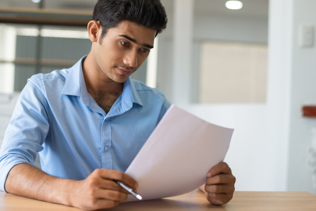 Pensive concentrated indian lawyer examining paper Free Photo