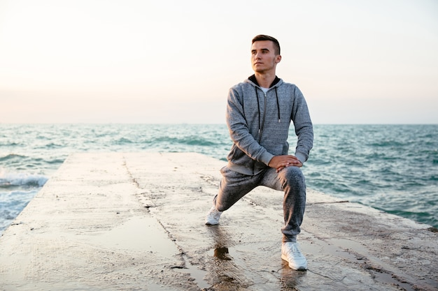 Pensive concentrated man in sportswear doing lunges, stretching Free Photo