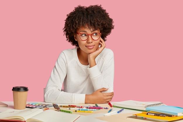 잠겨있는 어두운 피부색의 학생은 혼자서 예술을 공부하고, 그림을 좋아하고, 안경을 쓰고, 사려 깊은 표정으로 옆으로 보이며, 선명한 머리카락을 가지고, 분홍색 벽에 고립 된 빈 시트가있는 메모장을 사용합니다. 무료 사진