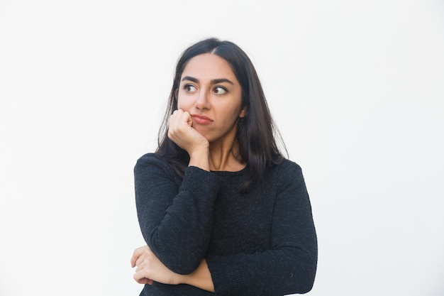 Pensive disappointed woman leaning chin on hand Free Photo