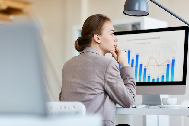 Pensive employee analyzing statistics Free Photo