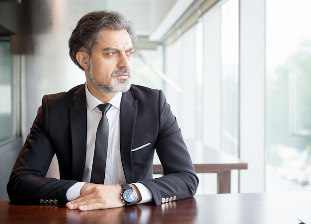Pensive Entrepreneur Sitting at Empty Desk Free Photo