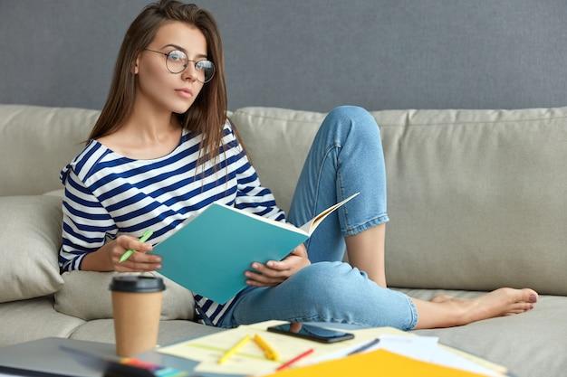 透明な眼鏡をかけた物思いにふけるヨーロッパの女性は、教科書とペンを持って、コースペーパーを渡す準備としてメモを書き留め、持ち帰り用のコーヒーを飲み、アパートのソファでポーズをとります。仕事のコンセプト 無料写真