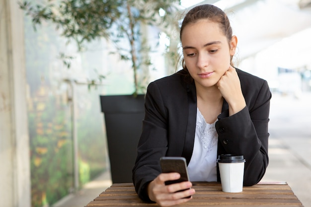 Pensive female office worker testing new mobile app Free Photo