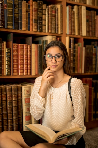 Pensive female student sitting with book in library Free Photo