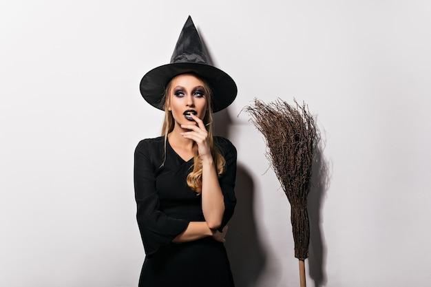Задумчивая женщина-волшебник позирует на белой стене. чувственная молодая ведьма в черной шляпе, стоя рядом с метлой. Бесплатные Фотографии