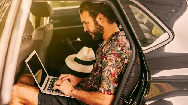 Pensive freelancer working remotely in car Free Photo