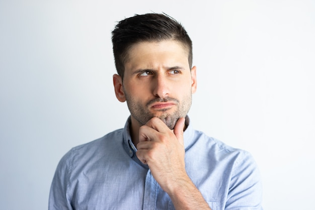 Pensive frowning guy in casual making decision Free Photo