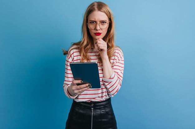Ragazza pensierosa in vetri che tengono compressa digitale. studio shot della bionda signora utilizzando gadget su sfondo blu. Foto Gratuite