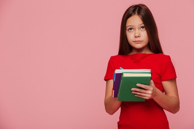 Pensive girl pupil looking at copy space and holding books Free Photo