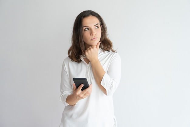 Pensive girl thinking over text message. Young Caucasian woman holding smartphone Free Photo