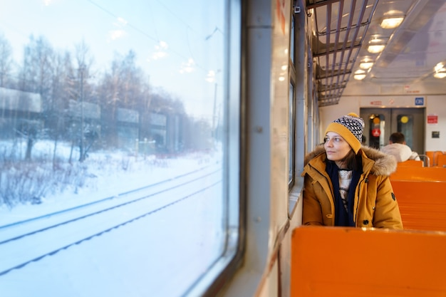Pensive girl traveling by local train in winter time, looking through the window at snowy landscape Premium Photo