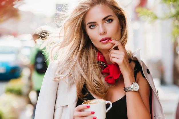 Задумчивая дама с темно-синими глазами позирует с чашкой чая, расслабляющейся после тяжелой недели Бесплатные Фотографии