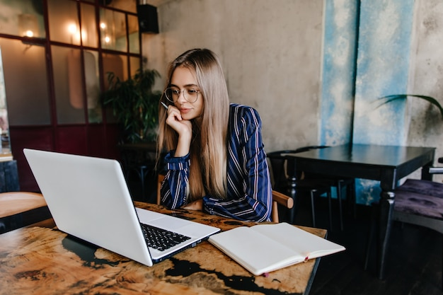Pensive long-haired girl in glasses looking at laptop screen. winsome brunette woman sitting in cafe with computer. Free Photo