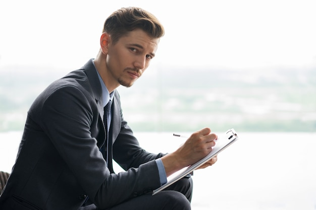 Pensive Look of Writing Middle-aged Businessman Free Photo