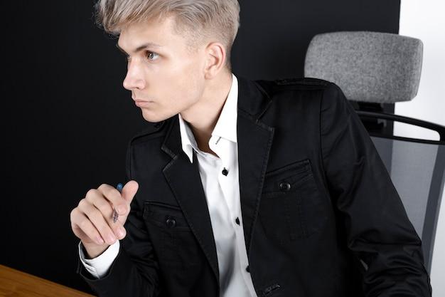 Задумчивый мужчина сидит за столом и думает о решении проблемы, вдумчивый сотрудник мужского пола обдумывает идею, смотрит в сторону, принимает решение Premium Фотографии