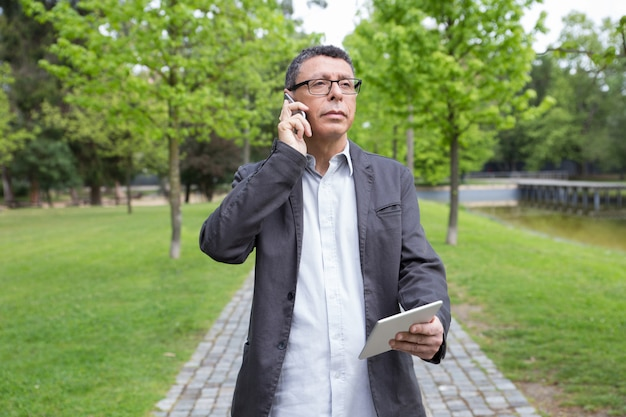 Pensive man using tablet and calling on phone in park Free Photo