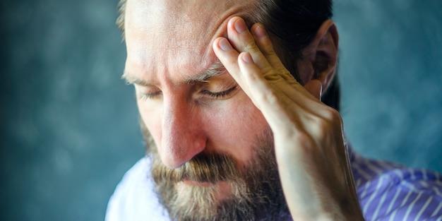 Pensive man with a beard massages the left temple Premium Photo