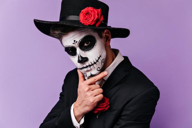 Uomo pensieroso con il trucco messicano tradizionale che osserva alla macchina fotografica. studio shot del ragazzo in abito da zombie in posa prima della festa di halloween. Foto Gratuite