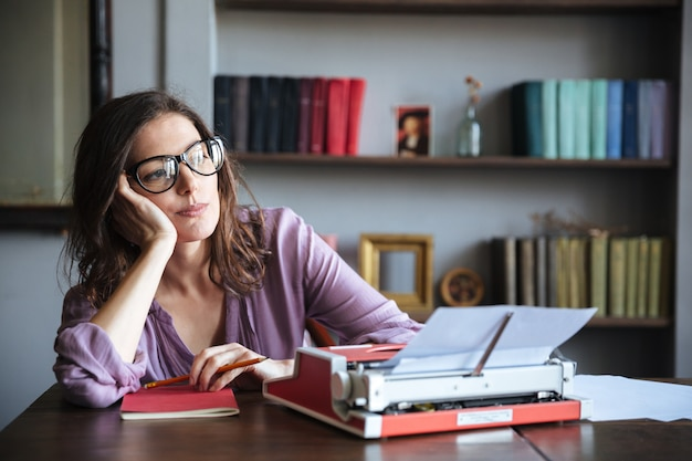 Pensive mature authoress in eyeglasses thinking and looking away Free Photo