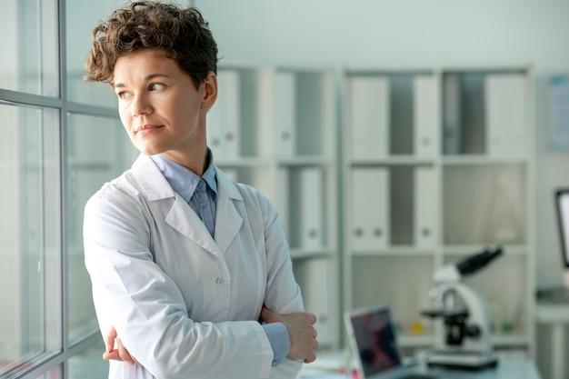 白衣を着た物思いにふける中年女性研究者が腕を組んで立ち、新しい実験を考えながら振り返る Premium写真