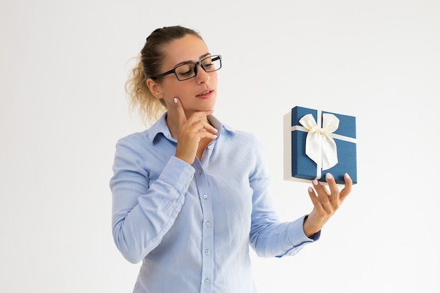 Pensive office girl in glasses guessing what in gift box Free Photo