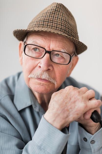 Vecchio pensieroso con occhiali e bastone Foto Gratuite