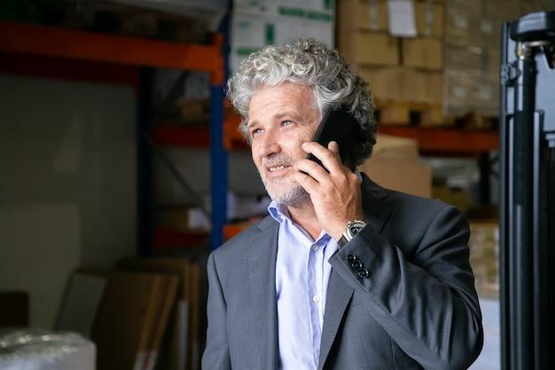 Imprenditore maturo positivo pensieroso in piedi in magazzino e parlando al telefono cellulare. ripiani con merci in background. copia spazio. concetto di affari o di comunicazione Foto Gratuite