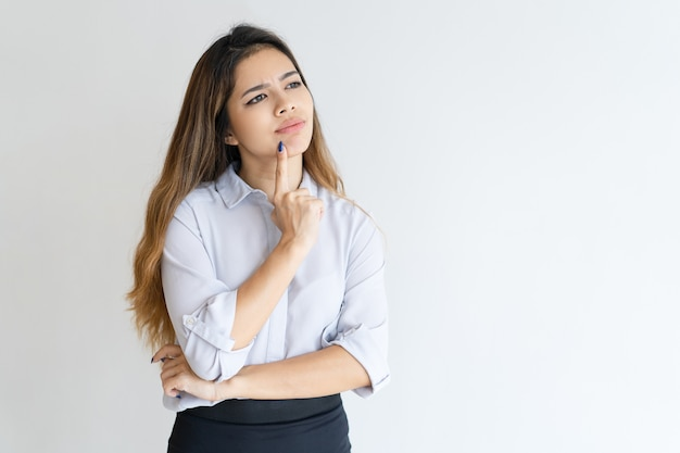 Pensive pretty woman touching chin with finger and looking away Free Photo