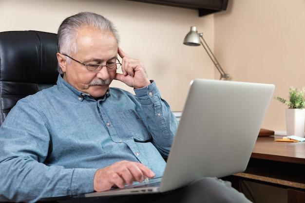 잠겨있는 수석 사업가 집에서 작동합니다. 안경을 쓴 노인이 노트북을 사용하여 원격으로 일하고 있습니다. Coronovirus 개념 중 원격 작업 프리미엄 사진