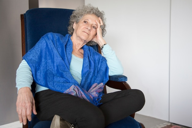 Pensive senior lady sitting in rocking chair and looking away Free Photo