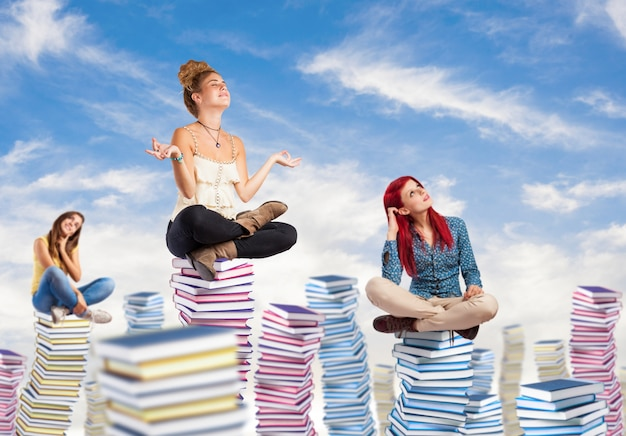 Pensive students sitting on columns of books Free Photo