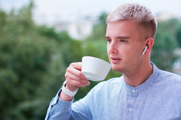 Pensive thoughtful guy drinking drink, tea or coffee from a cup. young man with gadgets in a shirt listening to music in wireless earphones outdoor. Premium Photo