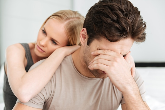 Pensive unhappy woman comfort her sad man while they sitting in bed Free Photo