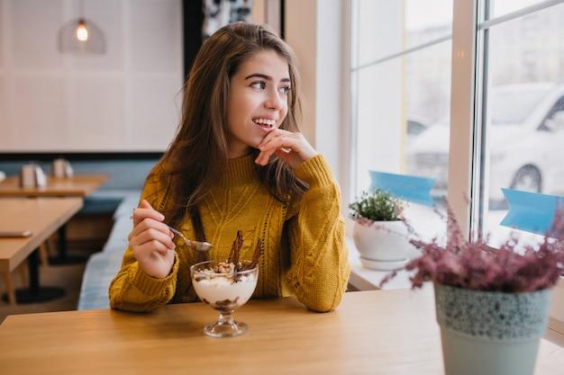 寒い日のカフェで休憩中にウィンドウを見てニットのセーターで物思いにふける女性。レストランでコーヒーを楽しんでいる黄色のシャツのロマンチックな女性の屋内ポートレート。 無料写真