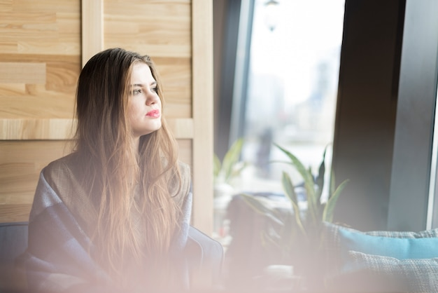 Pensive woman looking through the window Free Photo