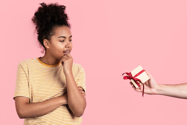 Pensive woman posing while receiving gift Free Photo