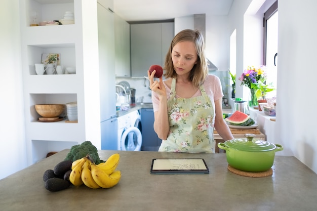 Pensive woman reading recipe on pad, holding fruit while cooking in her kitchen, using tablet near saucepan and fresh vegetables on counter. front view. cooking at home and healthy eating concept Free Photo