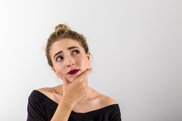 Pensive woman on white background. looking up with space for text Premium Photo
