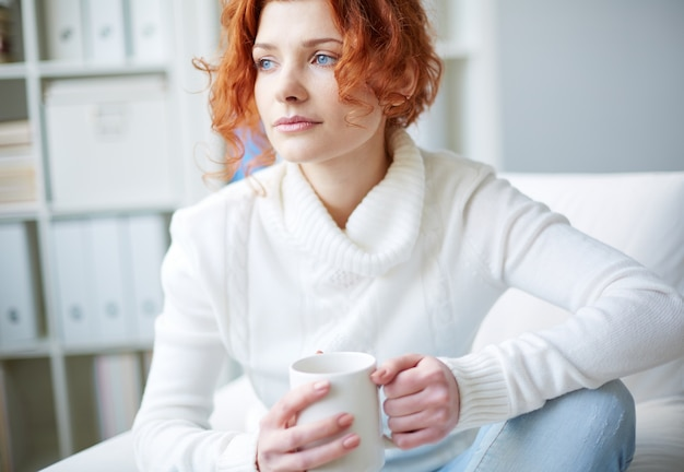 Pensive woman with a white sweater Free Photo