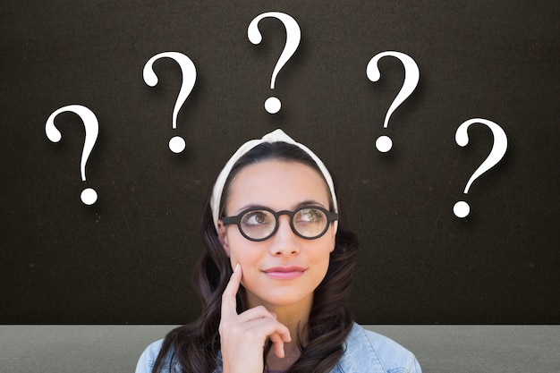 Pensive woman with question marks Free Photo