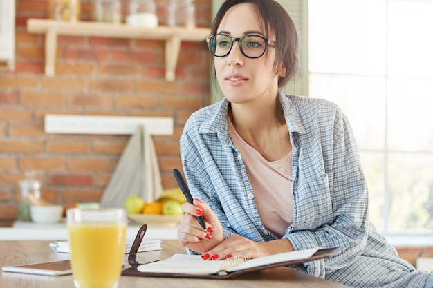 Pensieroso giovane imprenditrice pianifica la sua giornata lavorativa, si gode i fine settimana, indossa abiti casual per la casa, Foto Gratuite