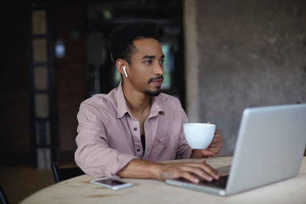 Pensieroso giovane maschio barbuto dalla pelle scura con cuffie wireless nelle orecchie che osserva da parte pensieroso mentre beve la tazza di caffè, seduto sopra il caffè della città con il laptop moderno Foto Gratuite