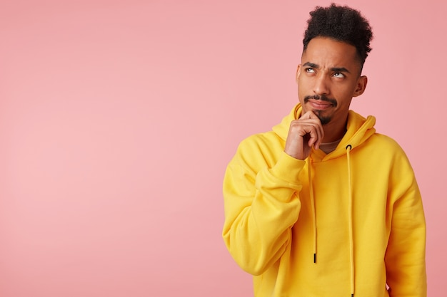 Pensive young dark skinned male with beard holding chin with raised hand and looking upwards with light smile, plotting something while standing in yellow sweatshirt Free Photo