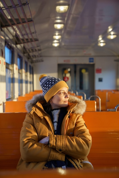 Pensive young european woman wear hat traveling by local train in winter time, crossed hands, looking through the window at sunset. Premium Photo