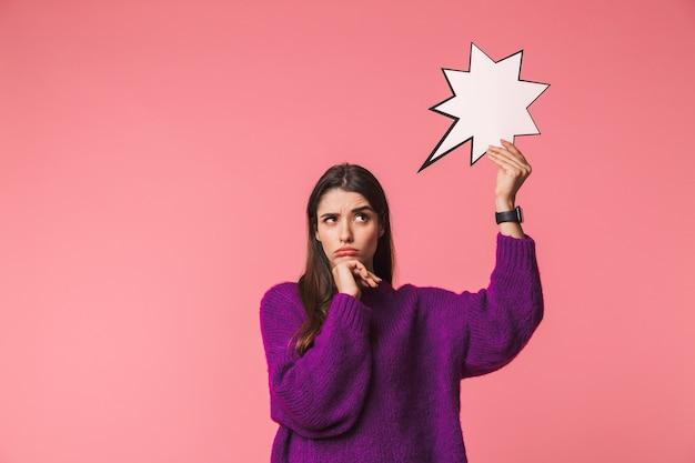 빈 연설 거품을 들고 핑크 이상 격리 서 스웨터를 입고 잠겨있는 어린 소녀 프리미엄 사진