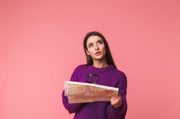 잠겨있는 어린 소녀 입고 스웨터 서 핑크 이상 격리, 가이드 맵에서 돋보기를 통해 찾고 프리미엄 사진