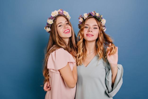 彼女の友人を抱きしめる軽い巻き毛の物思いにふける若い女性 無料写真